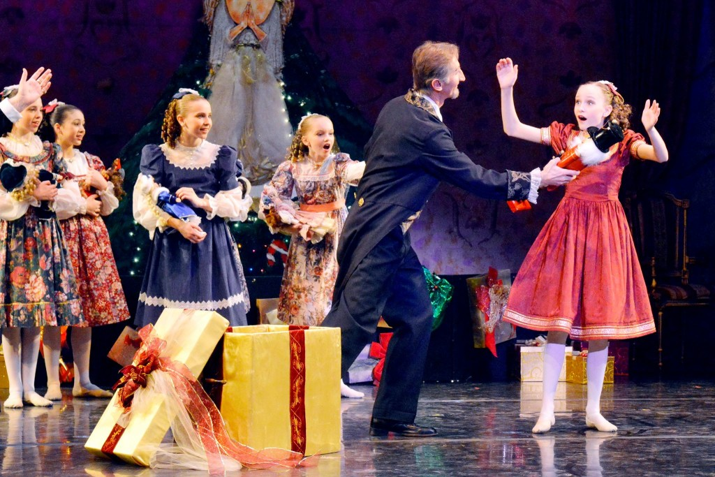 Herr Drosselmeyer (P. Kaupas) presenting Clara (Taylor Y.) with the toy Nutcracker in front of her party girl friends (L to R: Fiona M. Stephanie R. Lauren S. and Olivia R.) Photo Credit: Kim Bratvold. Jeunesse Classique Ballet