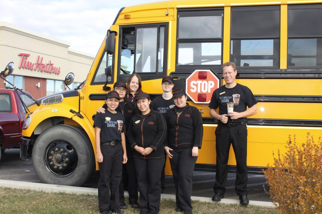 Tim Hortons High River staff in front of one of FSD's big yellow school buses during School Bus Safety Week