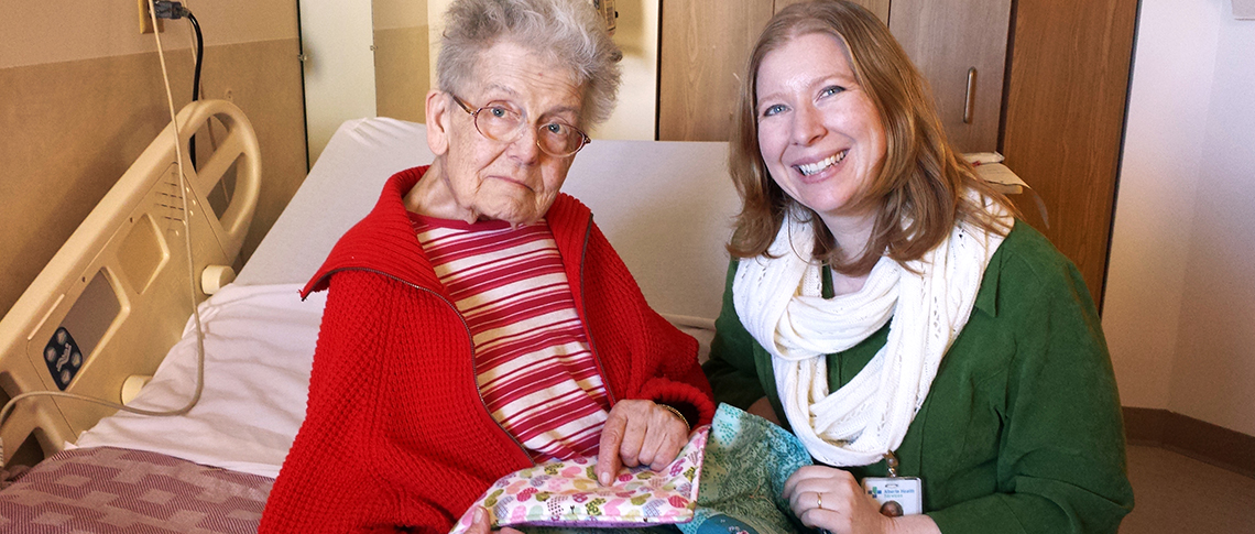 Glenrose Rehabilitation Hospital patient Isabel Pearson, with volunteer co-ordinator Kara Cooper, says she loves the hearts on her new quilt, a gift of Bethel Lutheran Church Quilters.