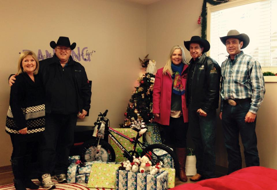 Rodeo Announcer Mike Labelle, Sun Country's Jody Seeley, Rodeo Clown, Dennis Halstead and Manager of Okotoks GM, Dan Katz surprise Rowan House residents with some special gifts.