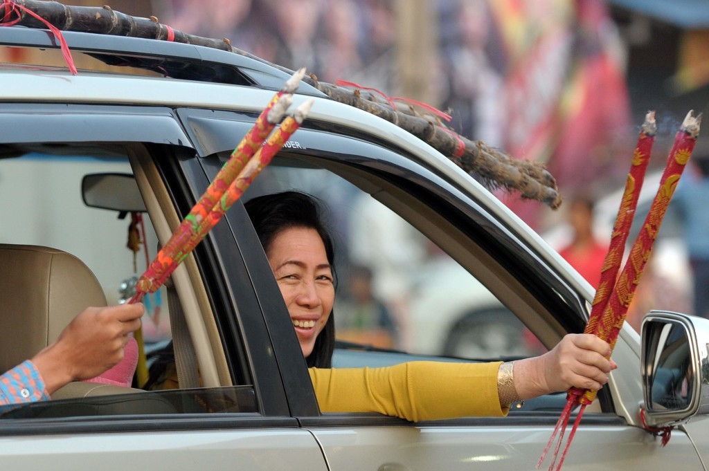 Cambodian-Chinese hold incense sticks through the windows of a car after visiting a temple to mark the start of the Lunar New Year in Kandal province on February 8, 2016. (Getty)