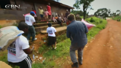 Christian volunteers take food to families in quarantine in their homes in a Liberian village because of Ebola.