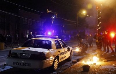 A protester jumps on a Ferguson police car set on fire by protesters in Ferguson, Missouri, November 25, 2014. (PHOTO: Reuters/Jim Young)
