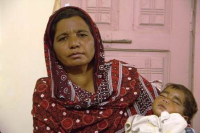 Parveen Bibi, sister of the murdered husband, holds the dead couple's baby - one of four children orphaned by the killing  4 Nov Punjab, Pakistan Asif Aqeel