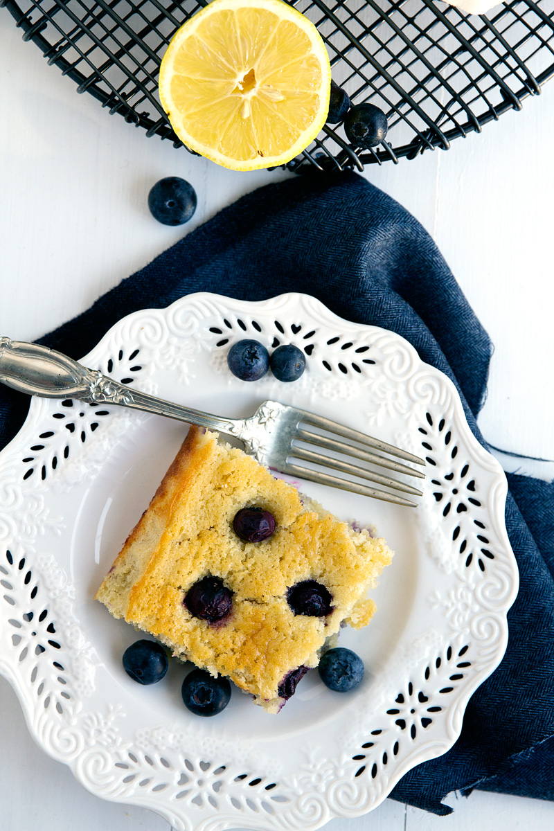 Lemon Blueberry Snack Cake - Simple cake in a pan with fresh blueberries and lemon for zest. Delightful!   gatherforbread.com
