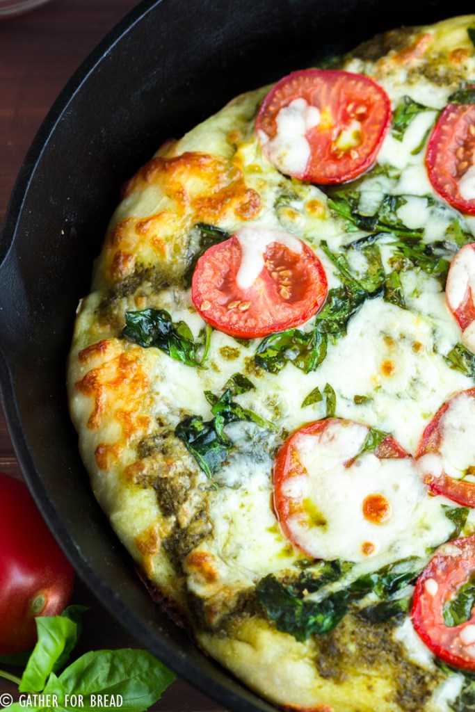 Skillet Pizza with Pesto Tomatoes and Spinach - Homemade pizza pie dough made in cast iron skillet with fresh pesto, tomato, and spinach toppings. Ready for Friday pizza night with these garden-fresh ingredients.