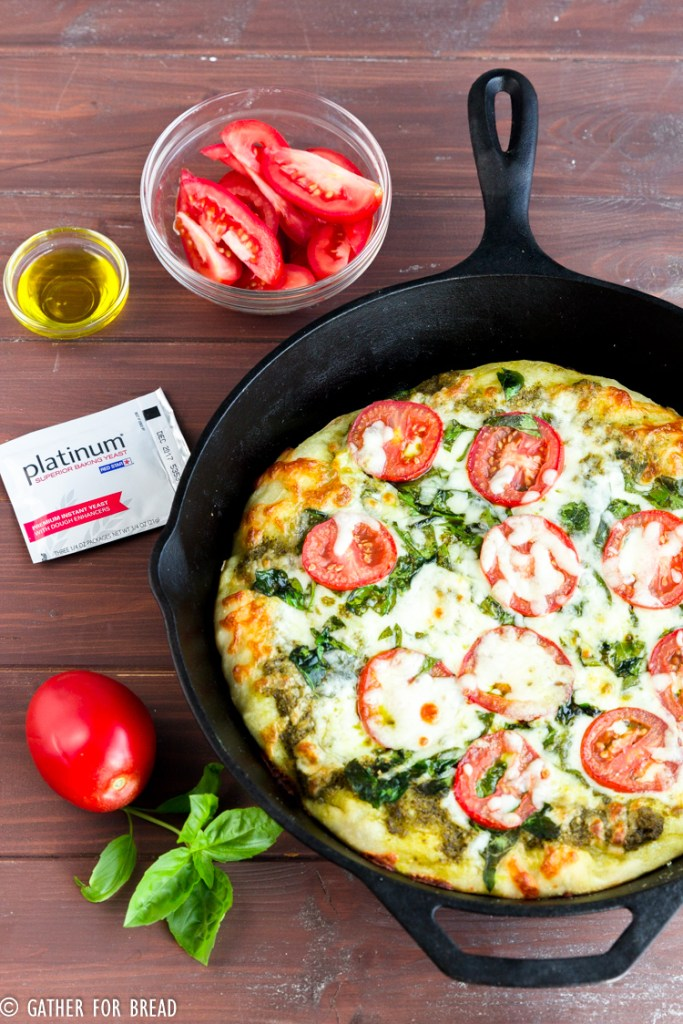 Skillet Pizza with Pesto Tomatoes and Spinach - Homemadepizza pie dough made in cast iron skillet with fresh pesto, tomato, and spinach toppings. Ready for Friday pizza night with these garden-fresh ingredients.