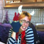 Cynical Woman poses with a crocheted zombie gnome.