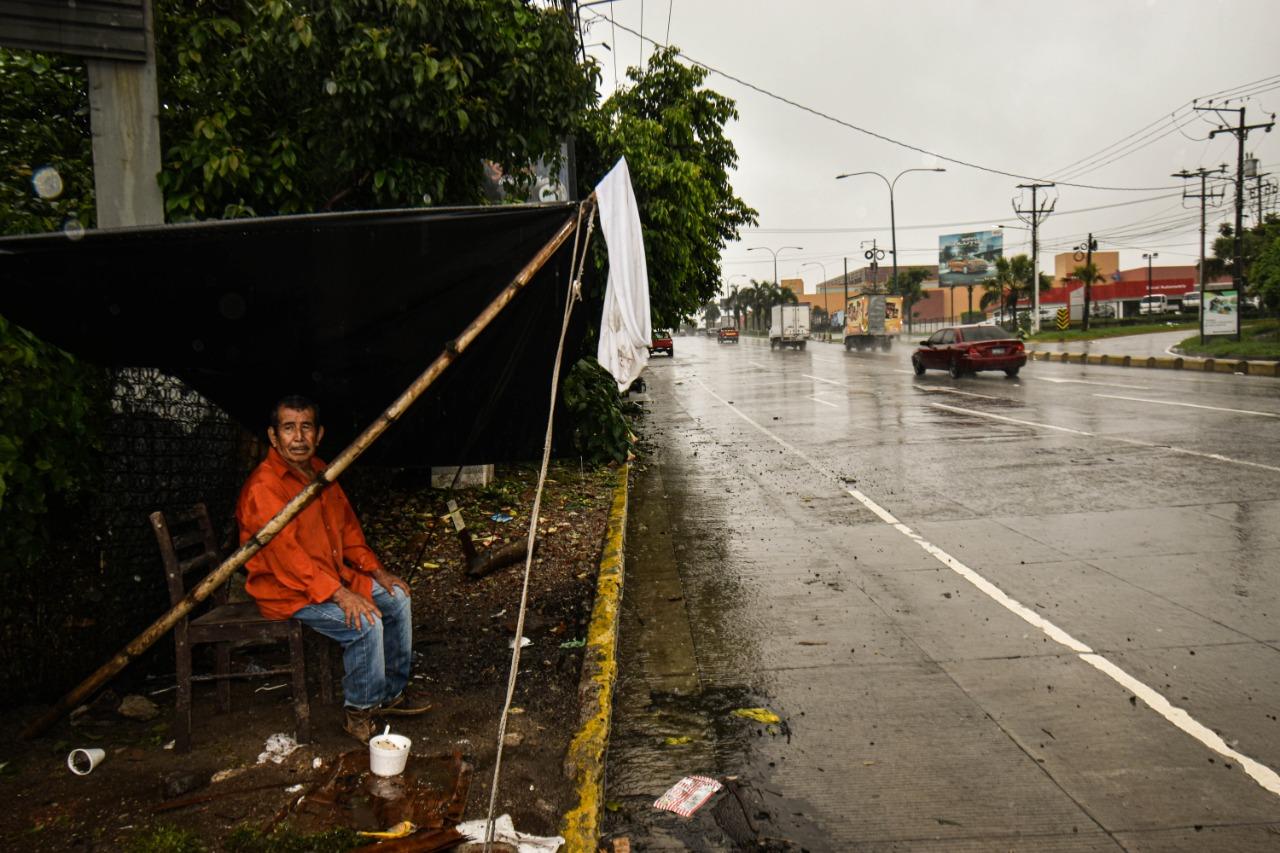"""Bajo la lluvia frente al lugar donde su casa fue destruida por la tormenta Amanda, Juan Manuel Mendoza, espera la llegada de ayuda bajo una bandera blanca. Miembros de la comunidad conocida como """"La Cuchilla"""" han perdido sus hogares en esta zona rodeada por centros comerciales y lugares de comercio. Foto/Emerson Flores"""