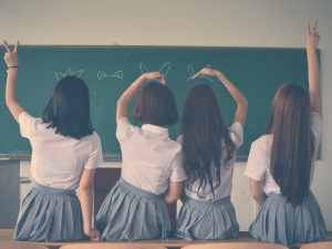 photo of four girls wearing school uniform doing hand signs 710743