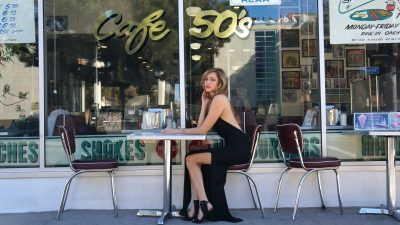 woman in black tank top and black skirt sitting on white chair