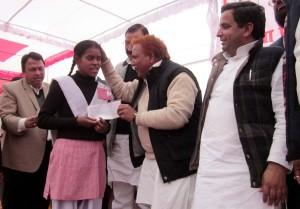 छात्रा को चैक देते राज्यमंत्री रामकरन आर्य, साथ में मौजूद सांसद धर्मेन्द्र यादव।