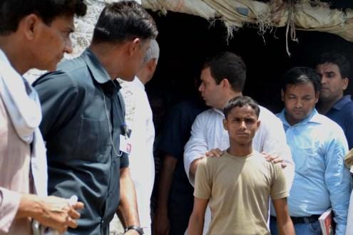 गाँव के लड़के के कंधों पर हाथ रख कर पीछे मुड़ कर सहज भाव से बात करते राहुल गाँधी