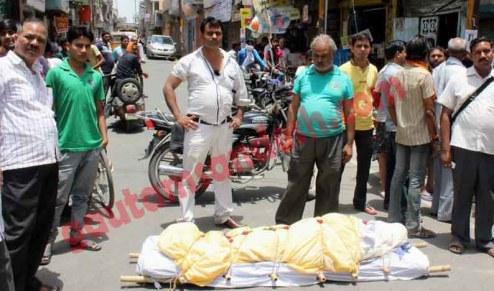 सड़क पर शव रख कर पुलिस के विरुद्ध प्रदर्शन करते आक्रोशित परिजन।