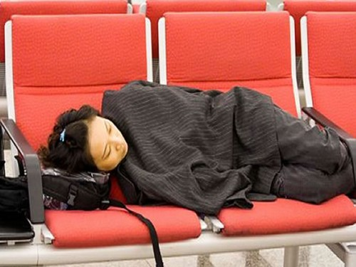A traveler catches up on sleep at an airport