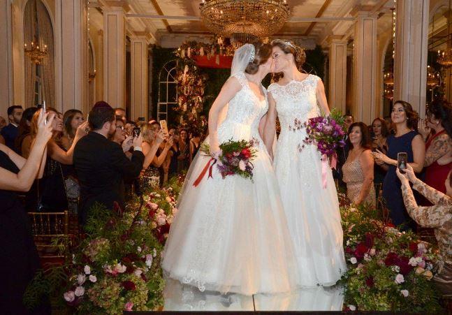As noivas fizeram seus vestidos com a mesma estilista,mas só se viram prontas na hora do altar. Jamais marcaram prova de roupa para o mesmo dia.