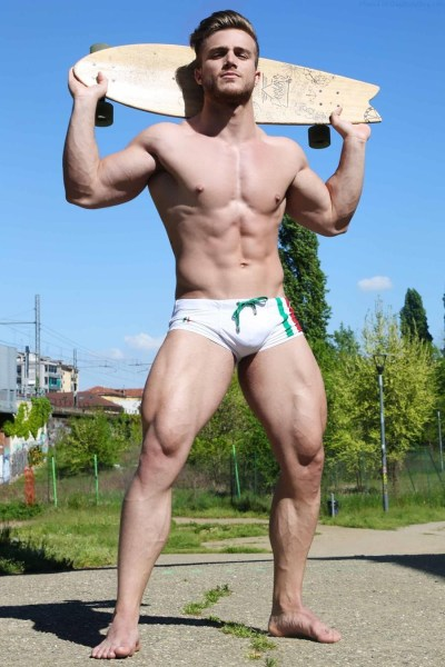 handsome jock model outside wearing bulging underwear and standing with a skateboard behind his head
