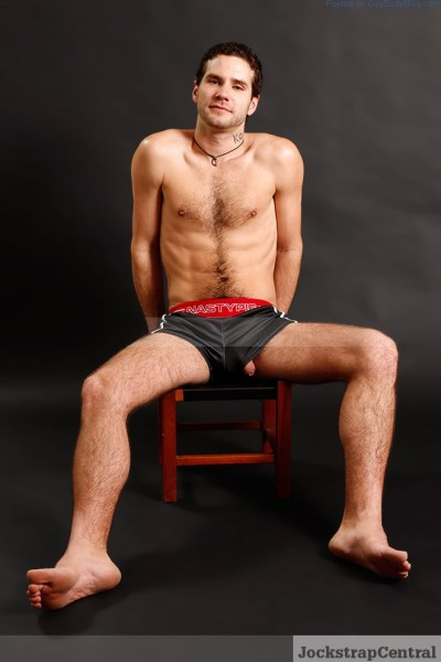 man sitting on a chair in shorts with his uncut penis peeking out of a leg hole