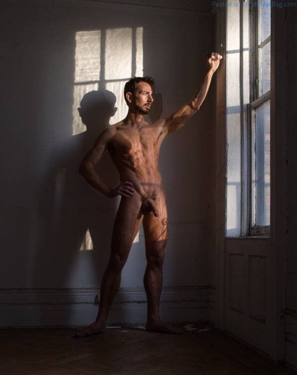hung naked man standing in the light from a window