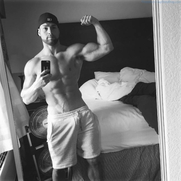 muscle man posing in a black and white selfie with his cock bulge showing in his sweat pants