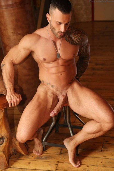 muscle man sitting naked with a long and hard uncut cock