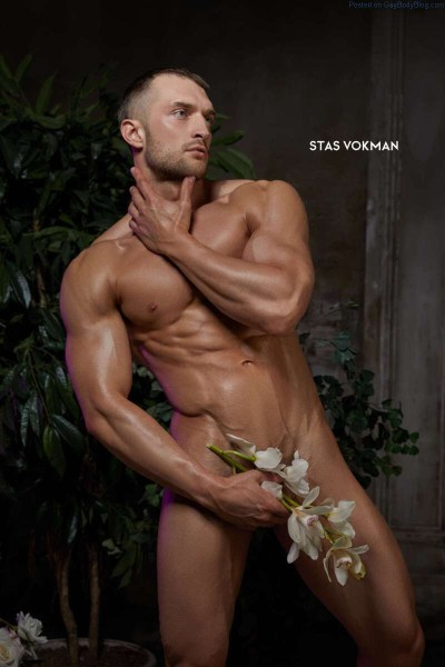 Naked muscle man posing with lilies hiding his cock