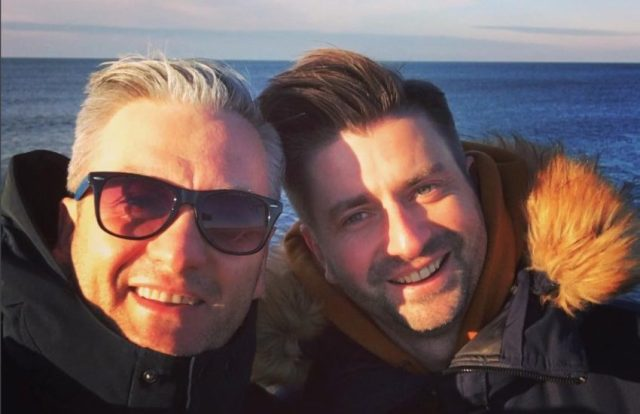Robert Biedroń and Krzysztof Śmiszek smiling in a selfie. it is a close up shot they are both wearing big winter jackets and there is a body of water behind them