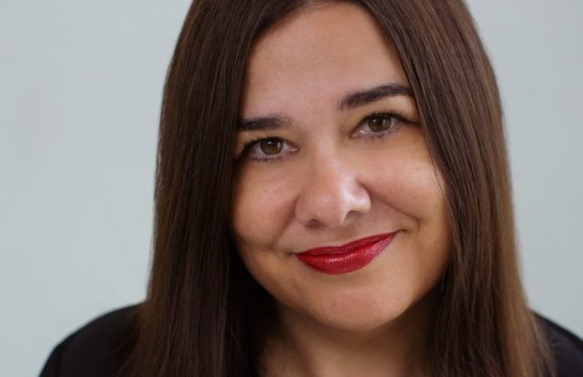 a head shot of jo hirst who has long brown hair and is wearing red lipstick.