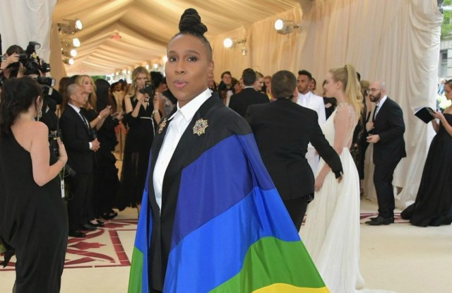 Lena waithe stands on the red carpet with a rainbow flag draped over her shoulders