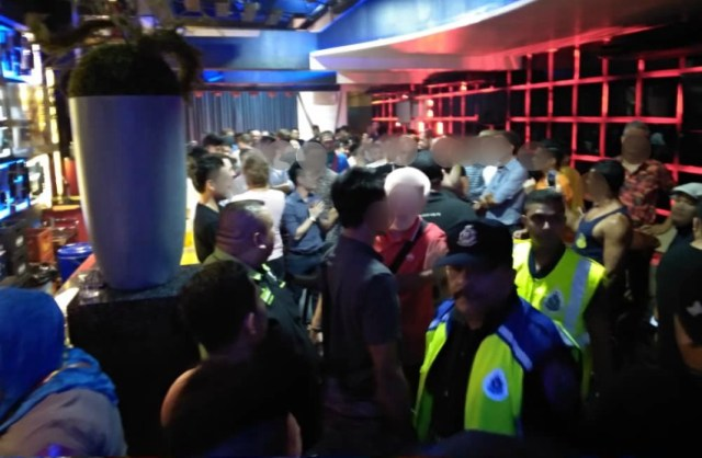 people stand around in a bar with police standing around in uniform