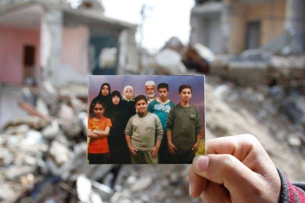 Holding the photo is Yassir Mahmood El Haj, 26, in Khan Younis refugee camp. His parents: Mahmoud Lutfi El Haj and Basma Abd El Qader El Haj, and his six brothers and sisters — Najla, 28; Asmaa, 22; Omar, 20; Tareq, 18; Sa'ad, 16; Fatma, 14 — were all killed, July 2014.