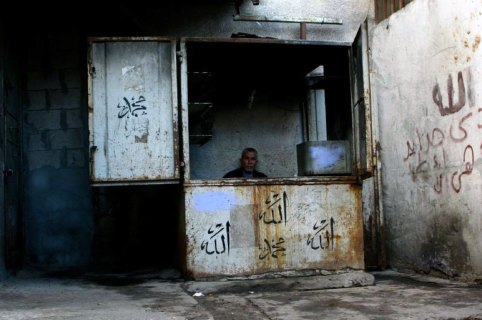 Man in an old booth, the names Allah and Mohammed written in the front