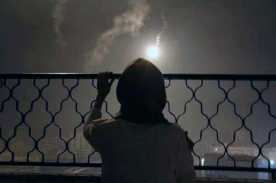 War on Gaza, summer 2014, Lara looks out at a flare dropped before a bombing