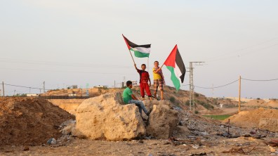 Three boys with two Palestinian flags