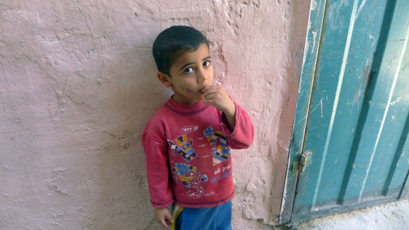 Young boy in pink against a pink wall in Jabaliya refugee camp