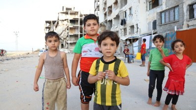 Five children with bombed apartment buildings behind them