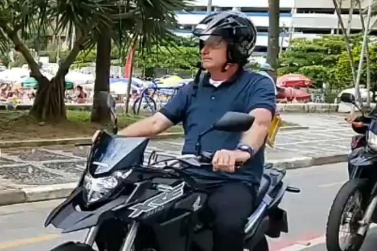 Bolsonaro é flagrando andando de moto sem afivelar capacete em Guarujá. Foto: Reprodução/Facebook