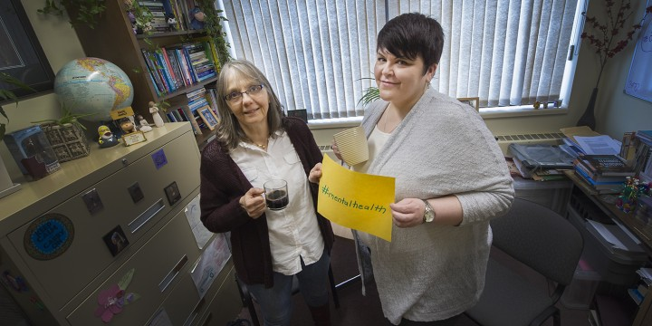 Nursing professors Joy Maddigan and Nicole Snow drink tea in an office.