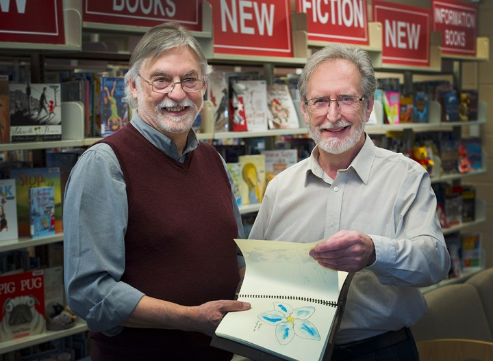 From left, Fred Hawksley and Alex Hickey look at the Great War field guide, in which the N.L. memorial flower the Forget-Me-Not can be seen.