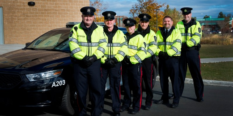 Six CEP officers in uniform stand beside a CEP patrol vehicle
