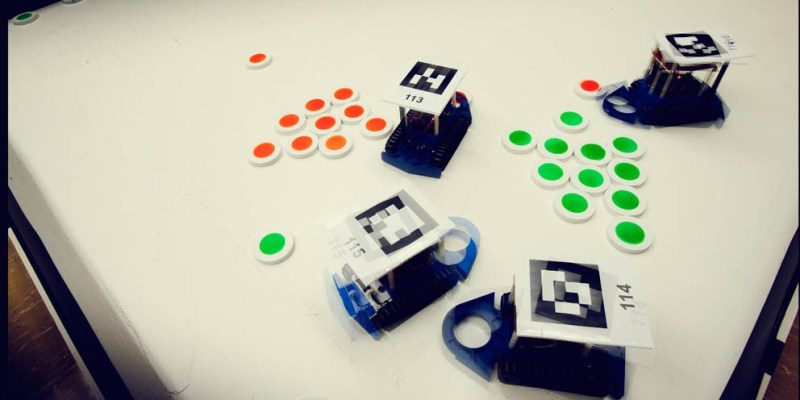 Robots sort pucks by colour