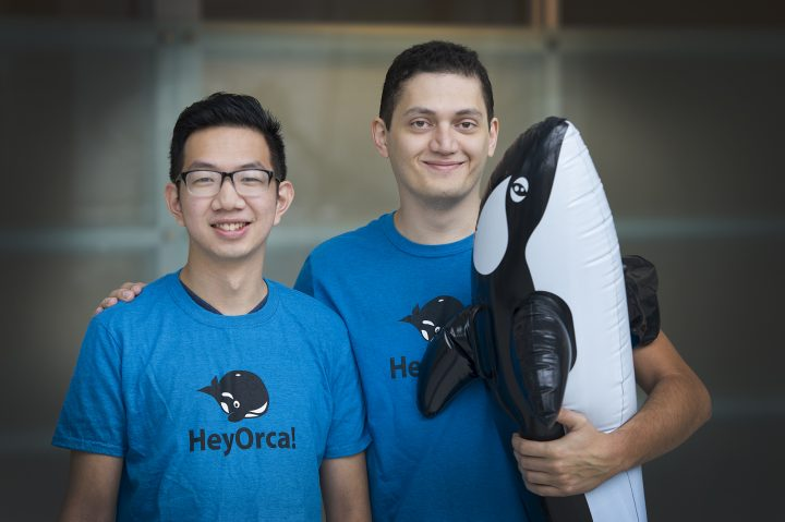 """Joe Teo and Sahand Seifi of HeyOrca! hold their mascot. They pass around the inflatable whale in meetings to indicate who has the floor. The whale is their """"conche"""" of sorts."""