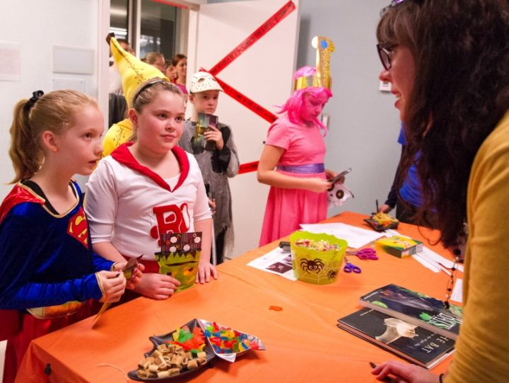 Trick-or-treaters taking in some science with their candy.