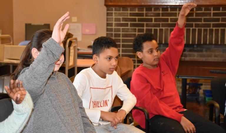 Students in Bishop Feild library put up their hands to speak