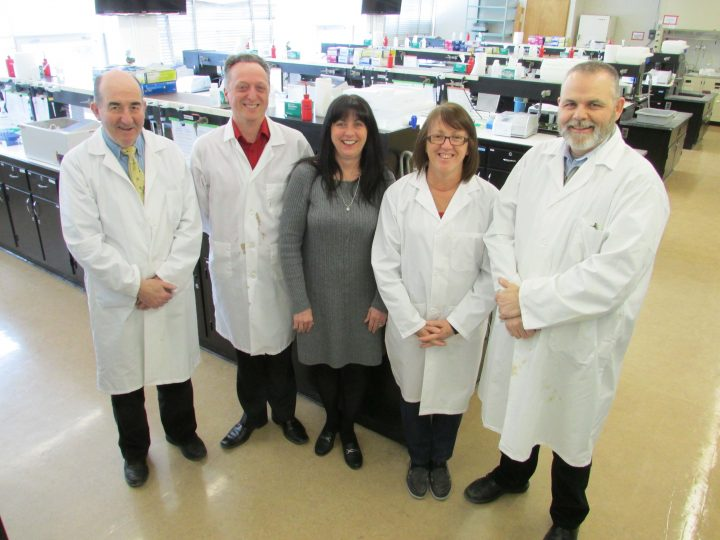 A recreation photo of the original five Biochemistry staff members. From left are Dr. Sean Brosnan, professor; Dr. Mark Berry, professor and head; Betty Ann Gaslard, secretary to the head; Marie Codner, student laboratory supervisor; and Craig Skinner, IT and instrumentation support.