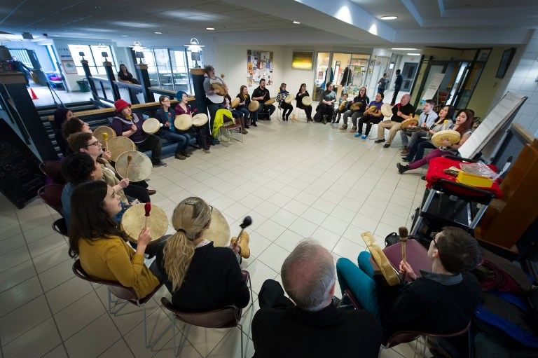 People sit in a circle in the University Centre while drumming together.