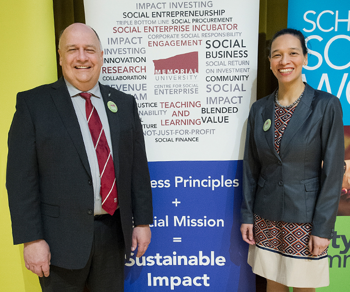 Dr. Gary Kachanoski, left, and Nicole Helwig pose in front of banners at the launch of the Centre for Social Enterprise, May 25.