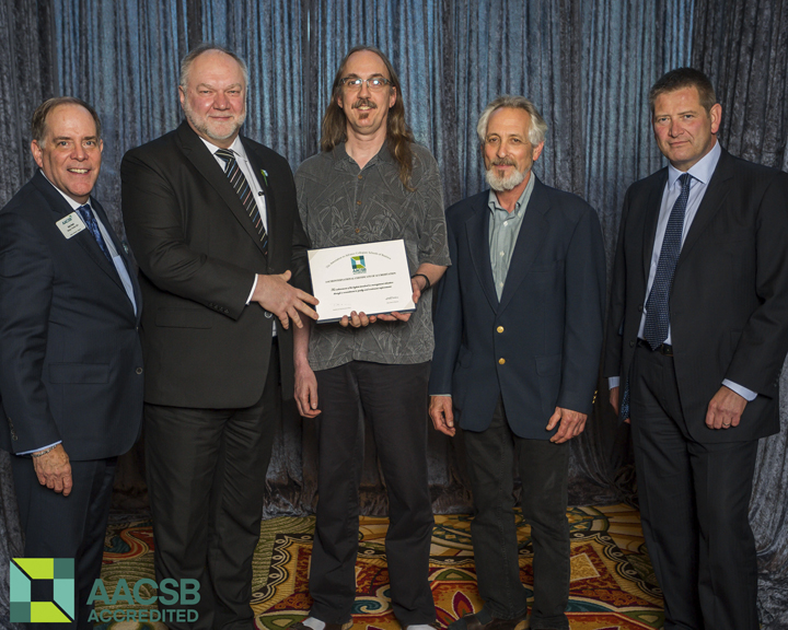 Dr. Wilfred Zerbe, second from left, and Dr. Larry Bauer, middle, pose with members of the Association to Advance Collegiate Schools of Business (AACSB) International.
