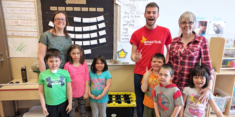 Nicky Thoms of Enactus Memorial (in red) poses with students from B. L. Morrison All Grade School in Postville, Labrador following a visit for Project Sucseed.