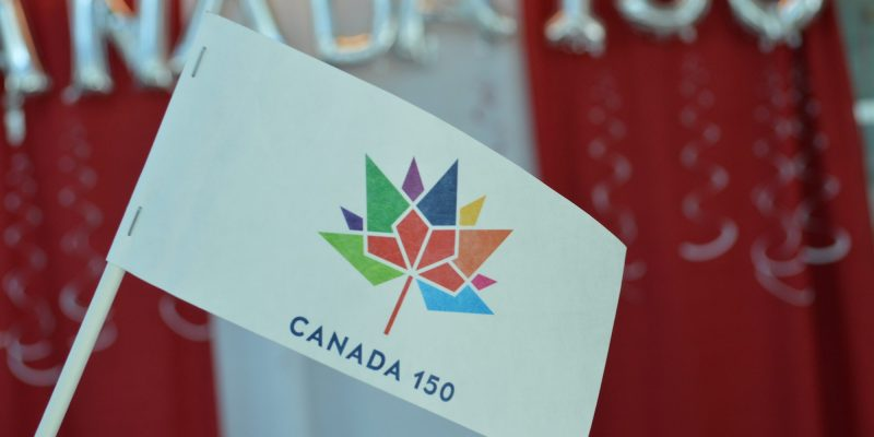 A photo of a Canada 150 flag, with a Canada 150 backdrop in the background.
